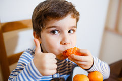 Four years boy eat a mandarin. 4-years boy eat a mandarin and show up his big finger royalty free stock image