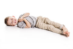 Four years boy lying on floor isolated on white Stock Photos