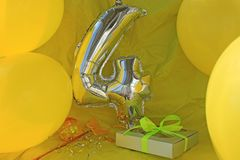 Celebration yellow background, a gift box with ribbon, magic ball and wand. Copy space. stock photography