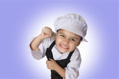 Four years chef girl. Portrait of a funny chef four years girl with angry face on purple background Stock Images