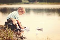 Four years old blond boy playing with paper boats on the water. stock photo
