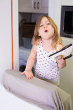 Little girl ironing in kitchen and complaining. Four years old blonde child with white shirt in the kitchen, ironing clothes and looking complaining Royalty Free Stock Photo
