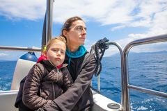 Daughter with dislike face expression with mother in motorboat. Four years old blonde girl looking at with dislike expression face, in arms of her mother stock image