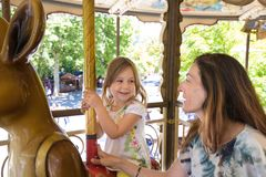 Little girl in carousel smiling and looking at mother Stock Photos