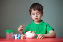 Four years old boy painting his piggy toy Royalty Free Stock Photo