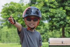 A four years old boy wearing sunglasses, a bike helmet. And  stands in a sunny park with trees and blue sky in the background Royalty Free Stock Photography