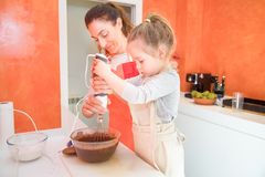 Girl beating chocolate cream with blender next to mother supervi Royalty Free Stock Image
