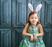 Four years old girl with bunny ears. Cute little girl with bunny ears staying against vintage blue door Royalty Free Stock Photography