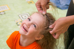 Four years old girl laughs she braided long hair Royalty Free Stock Photography