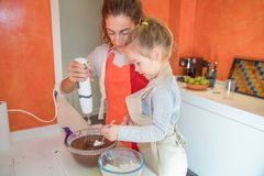 Girl pouring flour on chocolate cream and woman whisking with el Royalty Free Stock Photo
