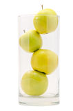 Four yellow apples in big glass Royalty Free Stock Image