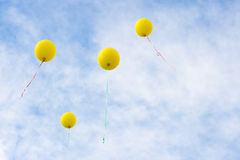 Four yellow baloons rising Royalty Free Stock Photos