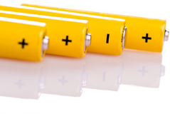 Four yellow batteries lying. Four yellow battery with positive and negative poles lying Stock Photography