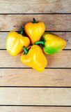 Four yellow bell peppers on table Stock Photos