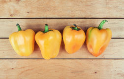 Four yellow bell peppers on table Royalty Free Stock Photo