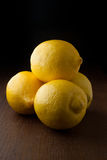 Four yellow fresh lemons on a wood table Royalty Free Stock Images