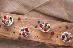 Four Yogurt, Granola and Berries on Wood and Burlap on a Slant Royalty Free Stock Photos