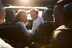 Four young adult friends travelling together in a car stock photos