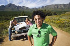 Four young adults consulting map beside jeep on dirt track in mountain valley, focus on man, smiling, portrait Stock Images
