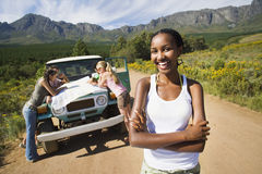 Four young adults consulting map beside jeep on dirt track in mountain valley, focus on woman, smiling, portrait Royalty Free Stock Photos