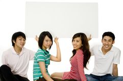 Four Young Adults With Sign Royalty Free Stock Photos