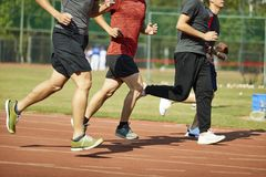 Young asian athletes competing on track. Four young asian track and field athletes racing competing against each other stock photography