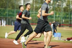 Young asian athletes competing on track. Four young asian track and field athletes racing competing against each other royalty free stock images