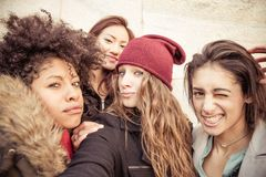 Four young beautiful girls smiling. Group of attractive young women of different ethnics taking a selfie - Four students smiling at camera - Best friends Stock Photos