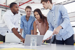 Four young business colleagues stand around laptop in office Royalty Free Stock Photo