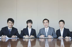 Four Young business people sitting in a row at a conference table, portrait Stock Image