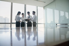 Four Young business people standing by conference table stock photo