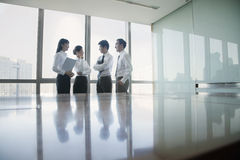 Four Young business people standing by conference table Royalty Free Stock Photography