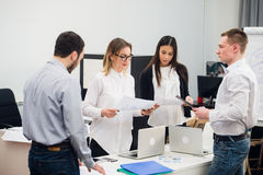 Four young business people working as a team gathered around laptop computer in an open plan modern office Royalty Free Stock Photography
