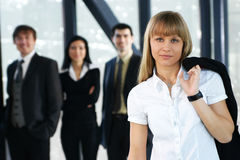 Four young business persons are standing as a team Royalty Free Stock Photo