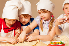 Four young chefs having fun making homemade cookie Stock Images