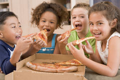 Four young children indoors eating pizza. Smiling Stock Image
