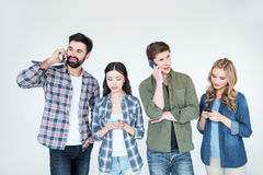 Four young friends in casual clothes using smartphones Stock Photo