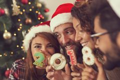 Welcome 2018. Four young friends holding Christmas cookies shaped as numbers 2018, having fun on a Christmas day. Focus on the guy on the left royalty free stock photography