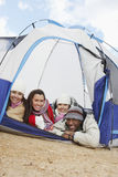 Four Young Friends Lying Down In Tent Royalty Free Stock Photos