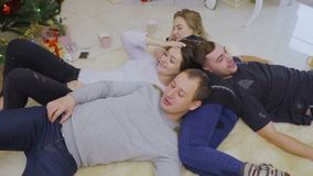 Four young friends relaxes on floor near Christmas tree stock footage