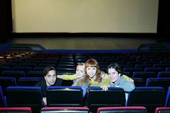 Four young friends sit on seats in cinema theater Stock Photo