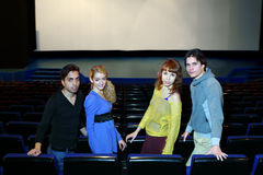Four young friends stand in cinema theater hall Stock Images