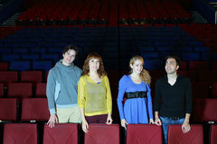 Four young friends stand in cinema theater royalty free stock photos