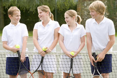 Four young friends on tennis court smiling Stock Photography