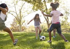 Four young girlfriends kicking football together in a park stock photography