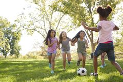 Four young girlfriends running after a football in the park royalty free stock image