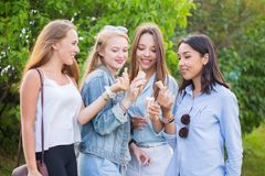Four young joyful student girls laughing and eating ice cream in the Park, outdoors stock photography