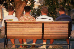 Four young men from back on bench Royalty Free Stock Photos