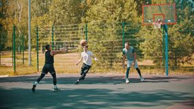 Four young men playing basketball on the sports ground. Mid shot stock footage