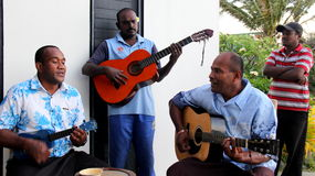 Four young men playing island music for guests visiting Fiji,2016 Royalty Free Stock Image
